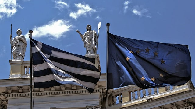 bandiera da la grezia e da l'uniun europeica sut statuas da deus grecs