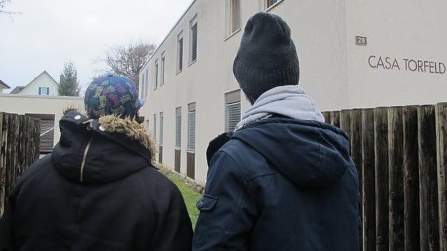 Asylsuchende vor grauem Hausblock in Buchs