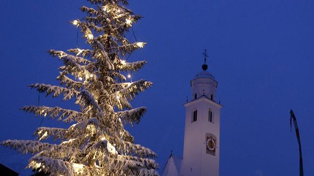 Beleuchteter Christbaum neben einer Kirche
