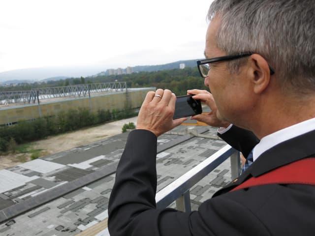 Regierungsrat Weber fotografiert von einer Hebebühne aus das brachliegende Gewerbegebiet.