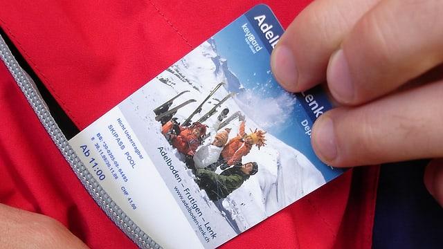 Eine Hand zieht eine Ski-Tageskarte aus einer Jackentasche.