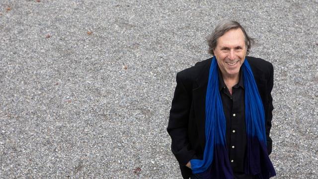 ein Mann mit schwarzem Mantel und blauem Schal