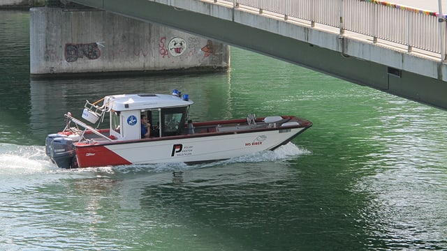 Ein Polizeiboot fährt unter einer Brücke hindurch.