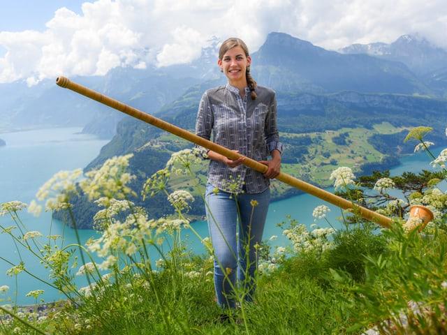 Màdchen mit Alphorn auf Aussichtspunkt über See.