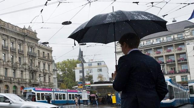 Mann in Anzug mit Regenschirm