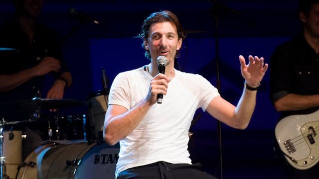 Fabian Cancellara sesa sin ina sutga cun in microfon en maun e discurra cun il public.