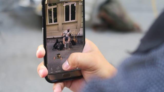 Handy mit einem Bild eines Strassenmusikers auf dem Display