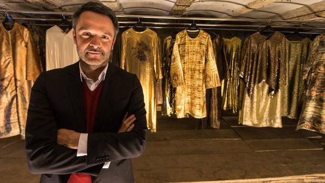 Giovanni Netzer vor Gewändern in der Garderobe.