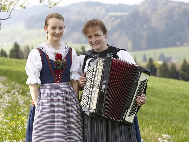 Die Jodlerin und die Akkordeonistin stehen auf einer grünen Wiese.