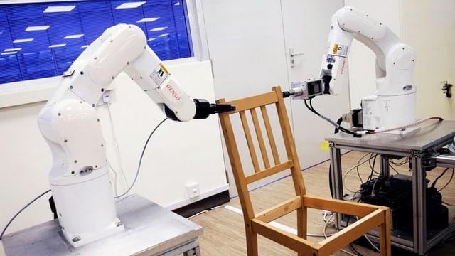 Zwei Roboter pecken mit ihren Armen an einen Stuhl.
