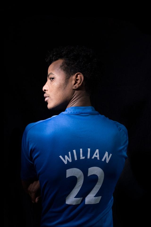 Ein Mann mit blauem Fussballleibchen.