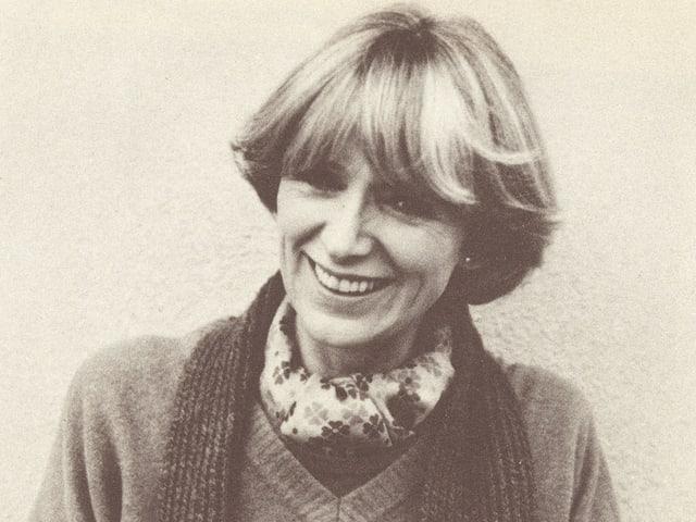 Porträt der blondhaarigen Moderatorin, die einen Strickpullover und einen Schal trägt.