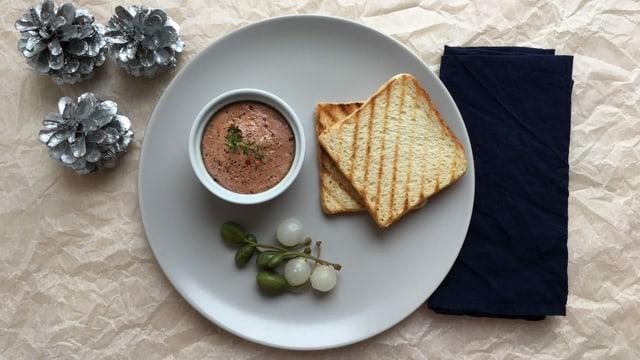 Ein Schälchen mit Hühnerleber-Paté, Kapern. Silberzwiebelchen und Toastbrotscheiben auf einem Teller.