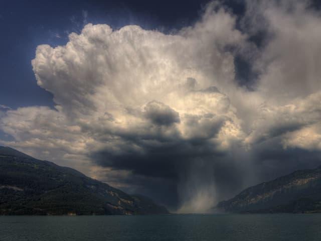 Ein Gewittertum steht über dem Brienzersee, der Regen ergiesst sich in den See.