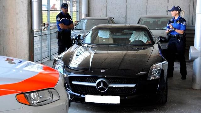 Eine Polizistin und ein Polizist stehen bei einem beschlagnahmten Auto.
