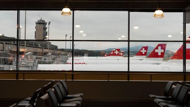 Blick aus einem Fenster des Flughafens Zürich auf stehende Flugzeuge.