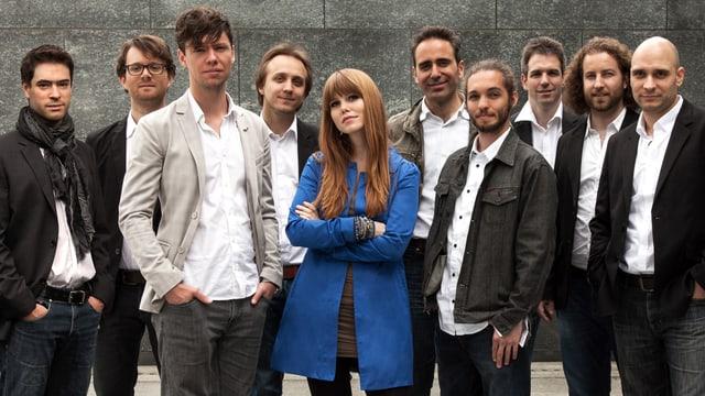 Luzia von Wyl - Ensemble: Neun Männer und eine Frau. Sie trägt aufällig blauen Mantel