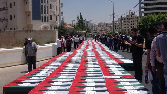 Rot-weiss-grüne Kartonsärge sind in einer langen Reihe auf einer Strasse aufgereiht.