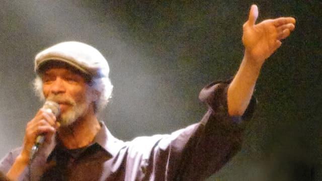 Ein älterer Schwarzer mit weissem Haar und Baskenmütze spricht in ein Mikrophon, den linken Arm ausgestreckt.