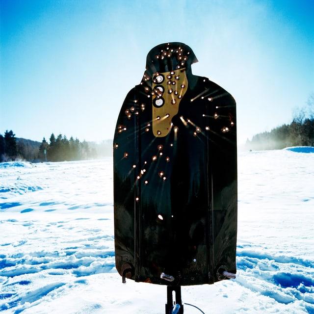 Zielscheibe im Schnee. Durch die Einschusslöcher dringen Sonnenstrahlen.