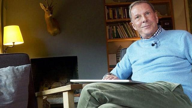 Ein älterer Mann sitzt im hellblauen Pulli und mit einem Buch in einem Sessel.