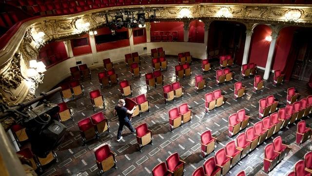 Ein Mann trägt einen roten Plüschsitz aus einem grossen Zuschauerraum, in dem die Sitzreihen durch Lücken unterbrochen werden.