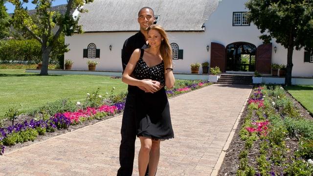 Charles Rees hält Jennifer Ann Gerber vor einem Landhaus im Arm.