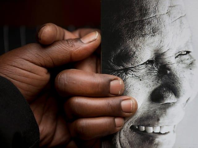 Schwarze Hände halten ein Bild von Nelson Mandela.