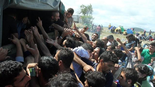 Flüchtlinge drängen sich um ein Fahrzeug und bitten um Wasser