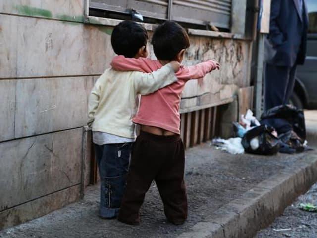 Zwei kleine Jungs stehen auf dem Trottoir.