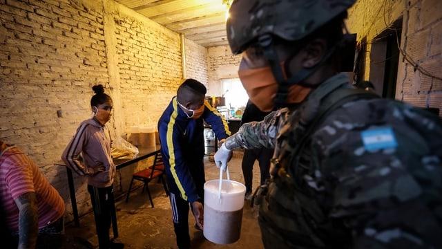 Soldat mit Gesichtsmaske, reicht Mann einen Eimer mit Essen.