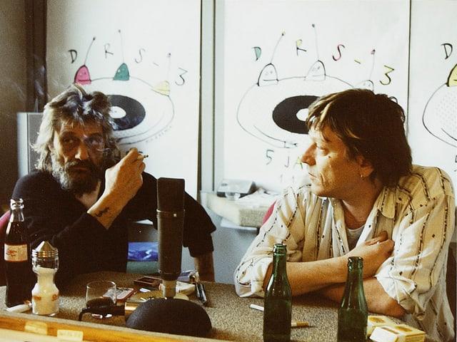 Zwei Männer an einem Tisch, auf dem unter anderem Bierflaschen stehen.