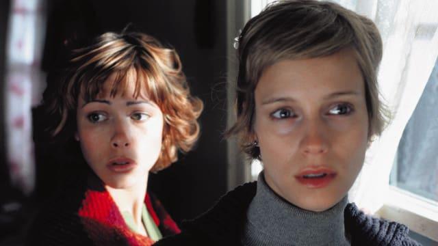 Zwei Frauen mit besorgten Blicken vor einem lichtdurchfluteten Fenster.