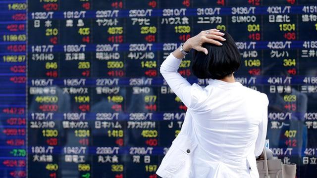 Frau schaut Börsenkurse an und hält sich den Kopf dabei