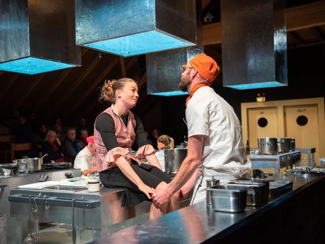 Ein Paar in der Küche schuat sich verliebt in die Augen.