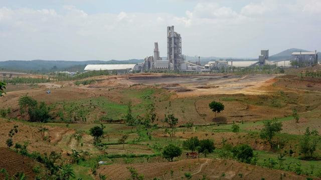 Eine Fabrik in einer kargen Landschaft.