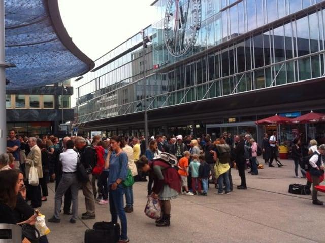Dutzende Menschen warten auf einem Platz.