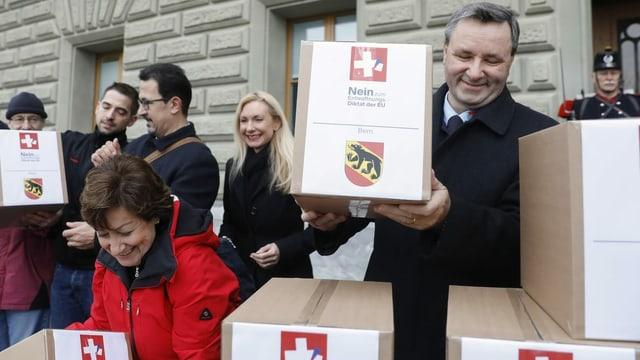Werner Salzmann und weitere Menschen bringen die Unterschriften in grossen Kartonboxen vors Bundeshaus.