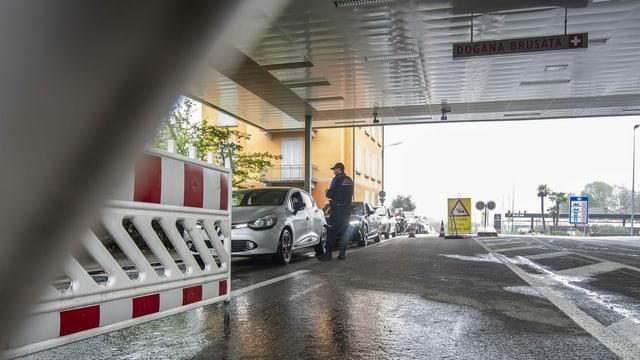 Schweizer Grenzwächter kontrolliert Autos am Grenzposten.