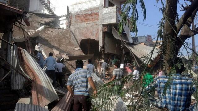 Ein Gebäude, das von einer Explosion zerstört wurde und vor dem sich Menschen versammeln