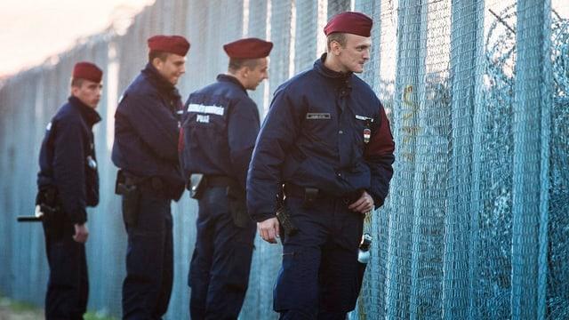 Grenzpolizisten wachen über einen Grenzzaun.