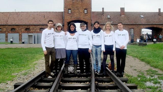 """Sieben Menschen stehen auf den Geleisen in Auschwitz. Sie tragen T-Shirts, auf denen entweder """"2nd gen"""" oder 3rd Gen"""" steht. Der Mann in der Mitte trägt ein T-Shirt, auf dem """"Survivor"""" steht."""