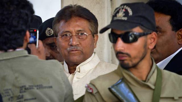 Musharraf neben Sicherheitskräften.