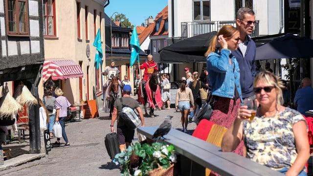 Touristen und zwei Ritter auf Pferden zwischen den historsichen Riegelhäusern in Visby/Gotland.