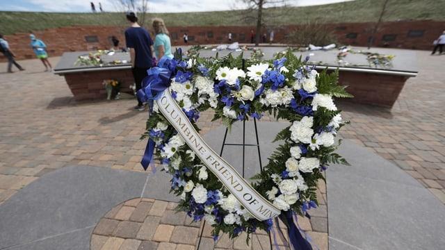 Purtret d'in cranz da flurs posiziunà davant in monument che commemorescha las 13 unfrendas da Columbine.