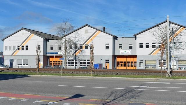 Drei neuere Häuser mit bunten Streifen, davor breite Strasse