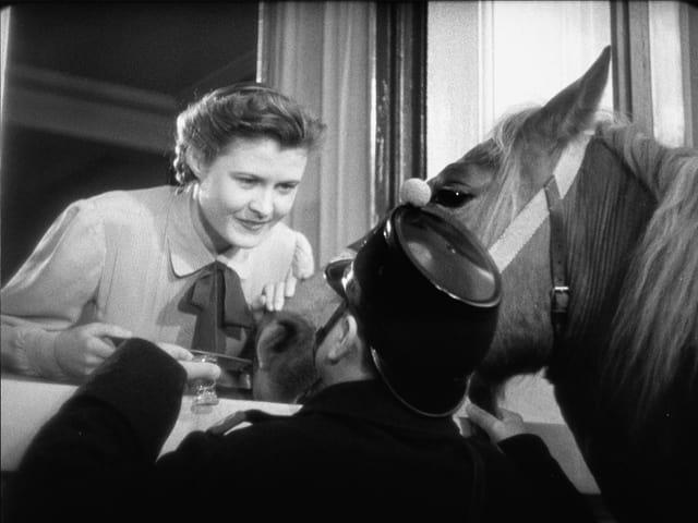 Eine Frau (Gilberte) lehnt sich zum Fenster hinaus zu einem Soldaten mit seinem Pferd.