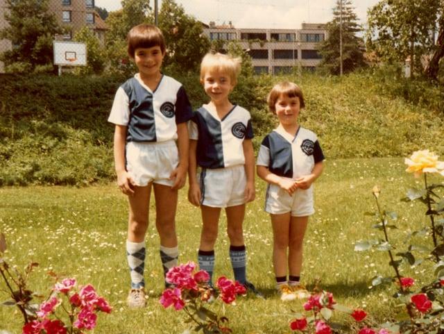 Zwei Buben und ein Mädchen in Fussball-Trikots.