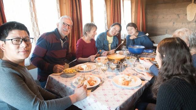 Menschen, die an einem Tisch Fondue essen.