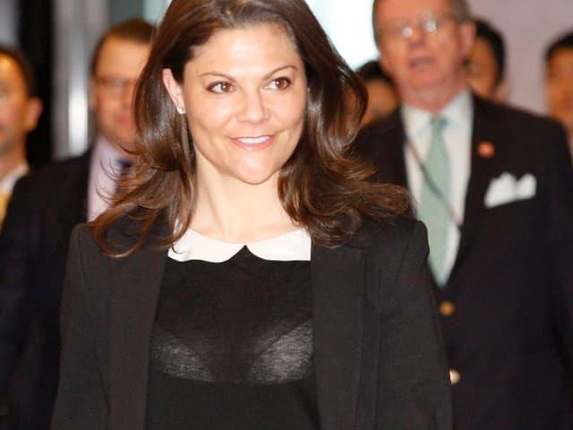 Victoria von Schweden mit hochgeschlossener schwarzer Bluse. Darunter sieht man einen weissen BH.